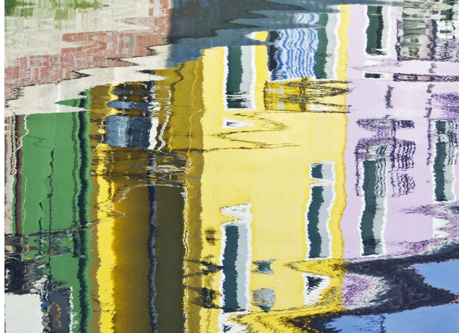 Ο αντικατοπτρισμός των πολύχρωμων όψενω των κτιρίων μέσα στο νερό θυμίζει πίνακα μοντέρνας τέχνης.