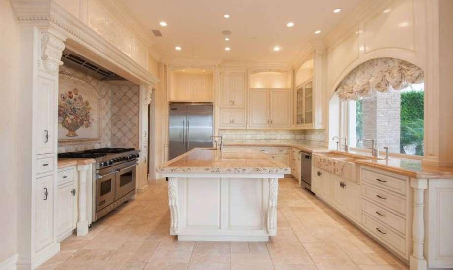 Στη κουζίνα κυριαρχούν τα γήινα χρώματα και το λευκό ξύλο.