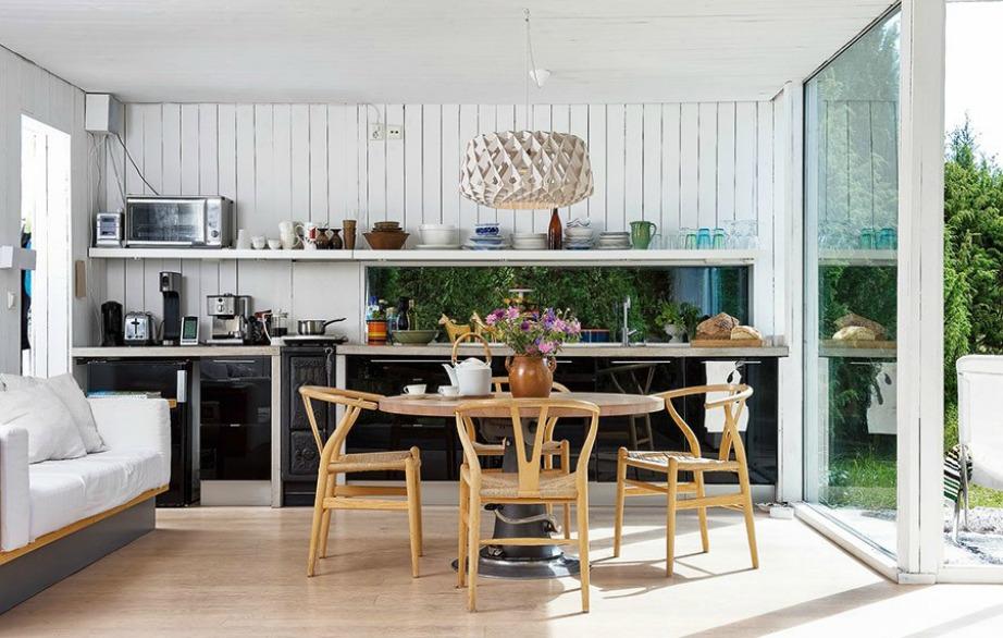 Σε αυτήν την κουζίνα συνδυάζονται λευκές με μαύρες επιφάνειες που ενισχύονται με ξύλο