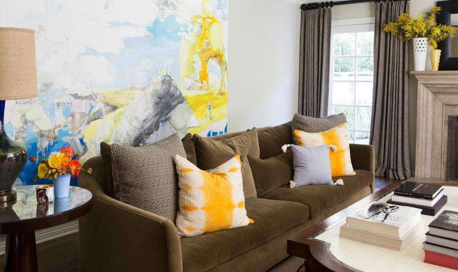 Ο υπέροχος πίνακας με τις έντονες αποχρώσεις και τα πολύχρωμα μαξιλαράκια αρκούν για να δώσουν χρώμα στο σαλόνι της Molly Sims.