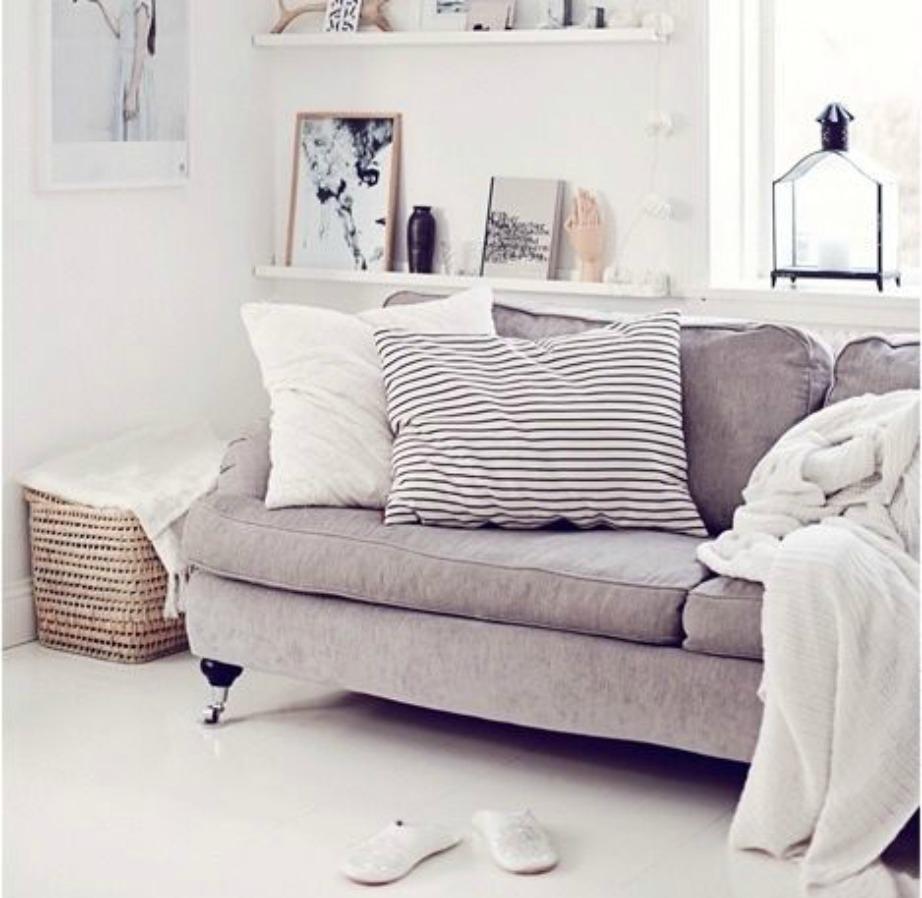 Γκρεζ καναπές διακοσμημένος με λευκά μαξιλάρια και ρχτάρι.