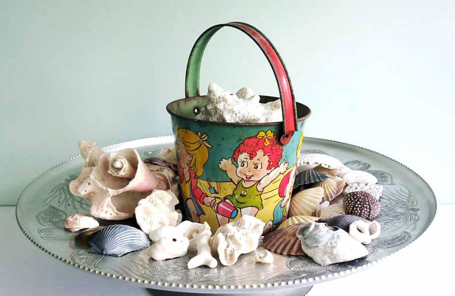Φτιάξτε μια ενδιαφέρουσα σύνθεση για την τραπεζαρία ή το coffee table σας γεμίζοντας ένα παλιό κουβαδάκι με βότσαλα και κοχύλια.
