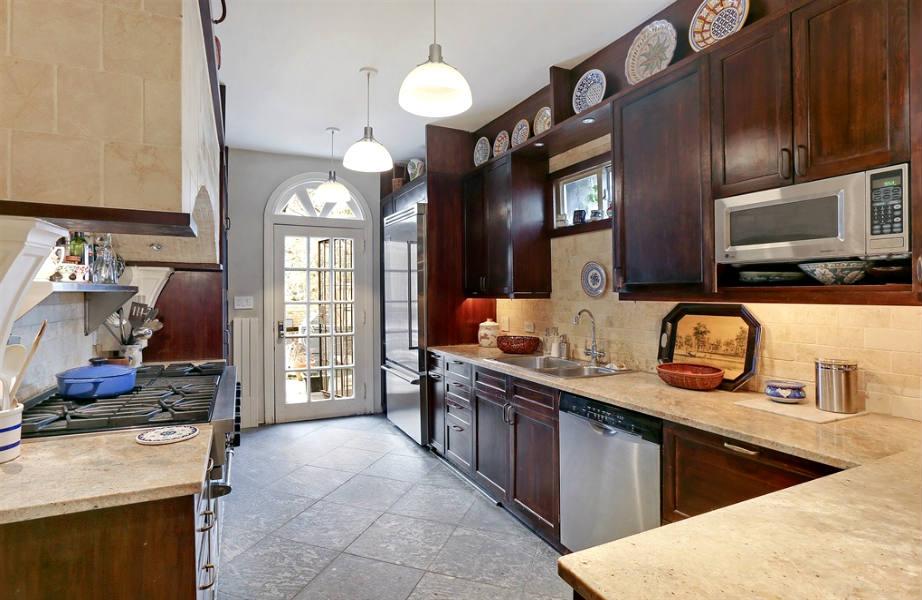 Η κουζίνα τα ξύλινα ντουλάπια από ξύλο κερασιάς συνδυάζονται με μεγάλες μαρμάρινες επιφάνειες.