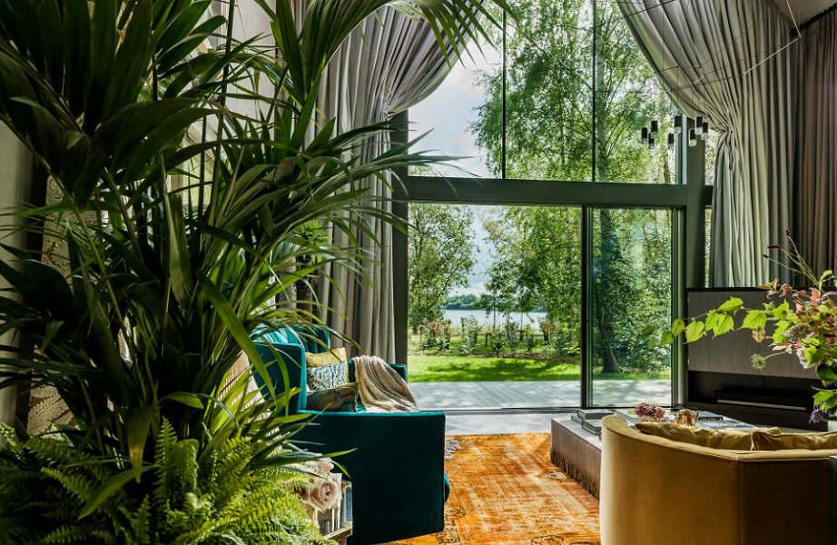 Οι αφράτοι βελούδινοι καναπέδες σε γήινες αποχρώσεις και τα φυτά χαρίζουν στο σπίτι μοναδική αίσθηση πολυτέλειας και ζεστασιάς.