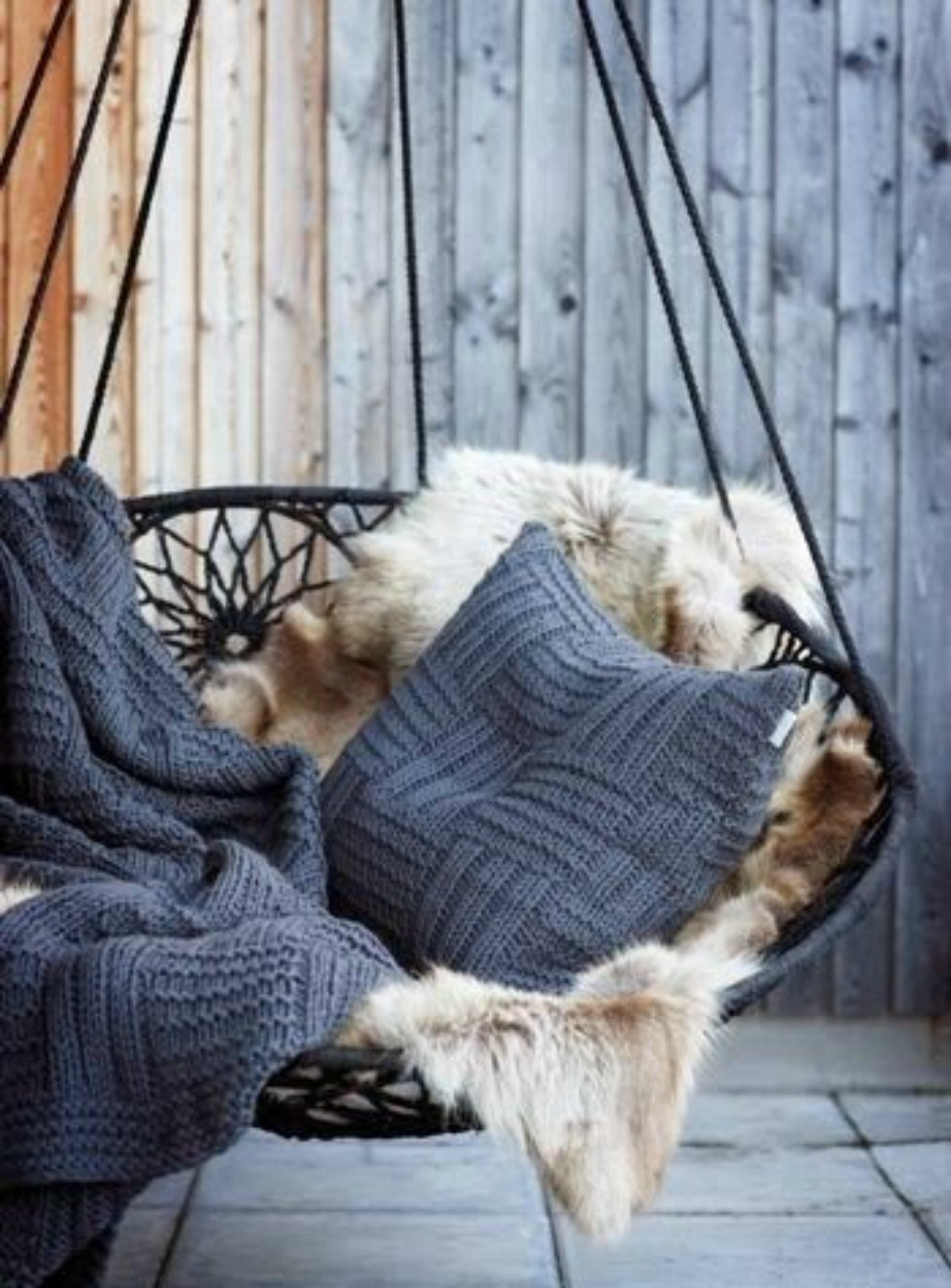 Μια κούνια με μαξιλάρια και γούνινη κουβέρτα είναι ό,τι πιο ωραίο διακοσμητικό έπιπλο για το μπαλκόνι σας.