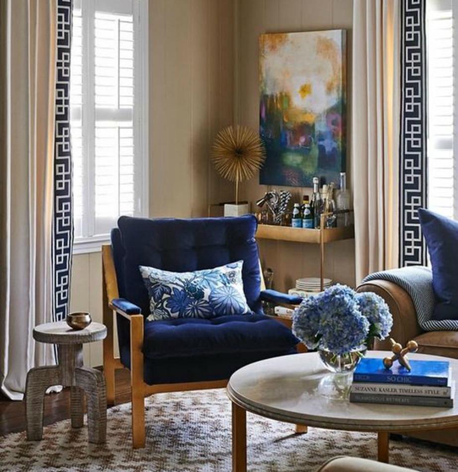 Οι κουρτίνες σε αυτό το σαλόνι είναι λευκές και στις άκρες έχουν σχέδια μαιάνδρου.