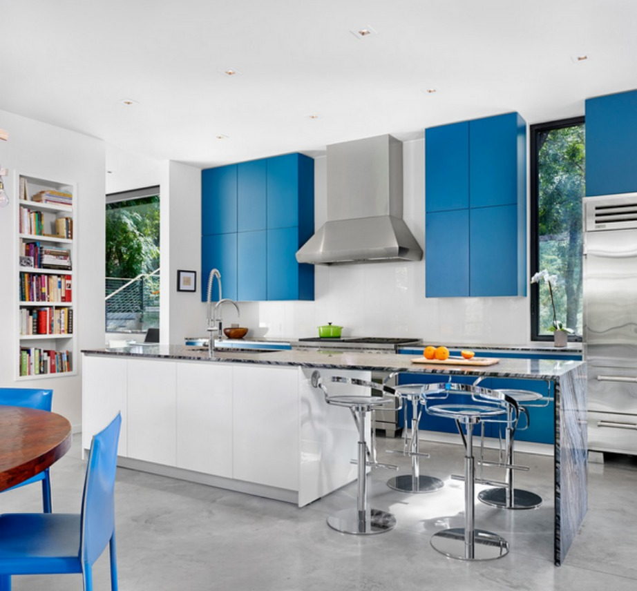 Τα μπλε ντουλάπια σε αυτήν την κουζίνα συνδυάζονται φανταστικά εμ τις μπλε καρέκλες. Ο λευκός πάγκος σπάει λίγο τη μονοτονία.