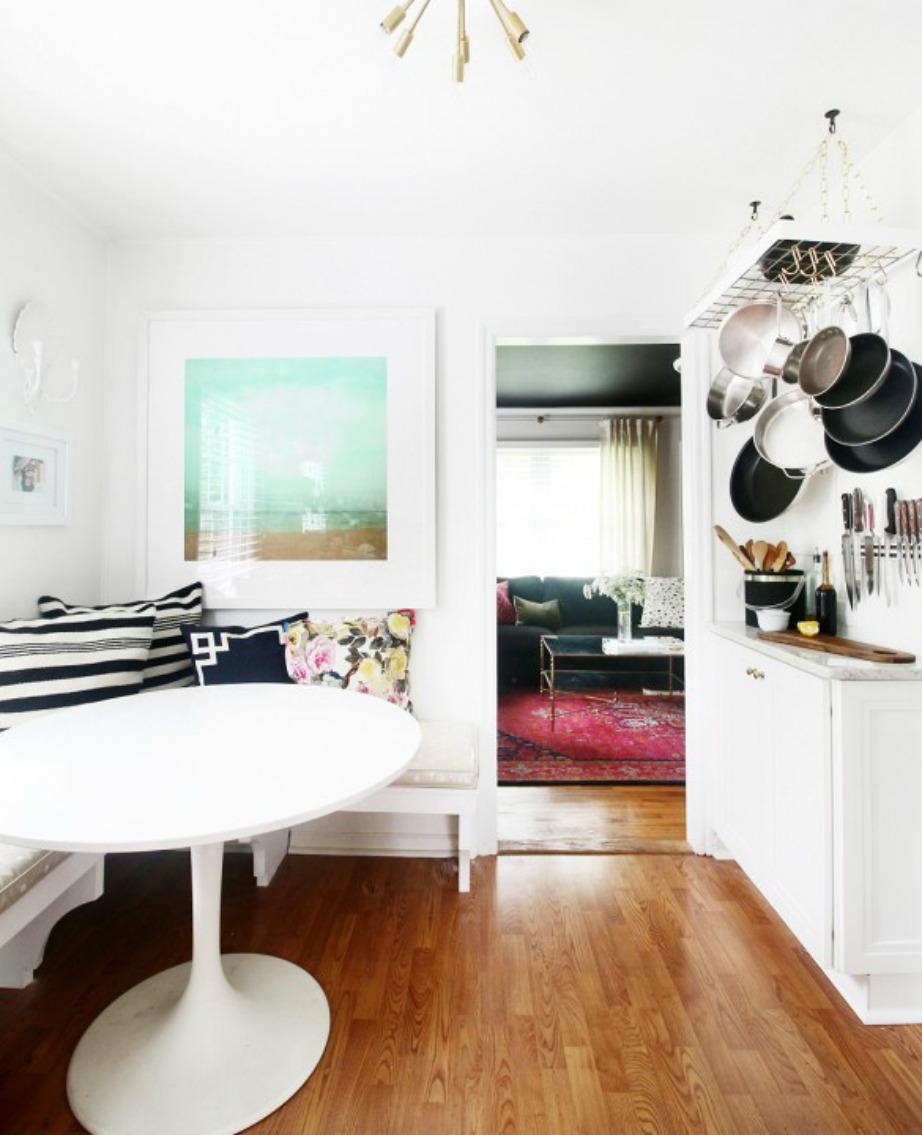 Στη μία γωνία τοποθετήθηκε ένα στρογγυλό λευκό τραπέζι και καναπές μα όμορφα μαξιλάρια.