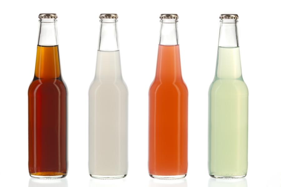 Four assorted soda bottles non-alcoholic drinks in glass