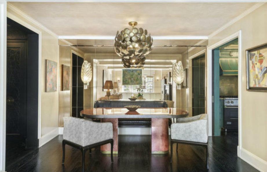 Μια ιδιαίτερη τραπεζαρία με εντυπωσιακά φωτιστικά, καθρέφτες και έπιπλα βρίσκεται κοντά στην είσοδο του σπιτιού.