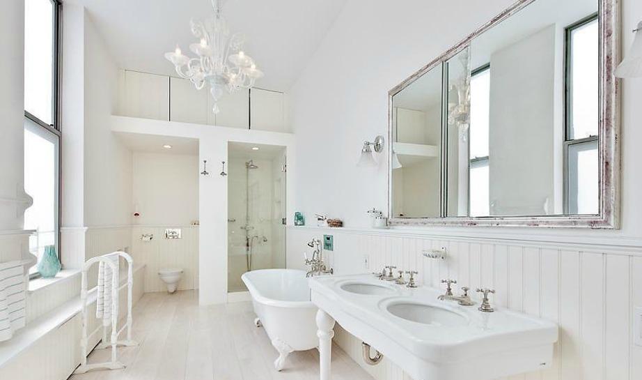 Οι ασημένιες λεπτομέρειες στις βρύσες αλλά και στον καθρέφτη σπάνε τη μονοτονία του λευκού που κυριαρχεί στον χώρο.