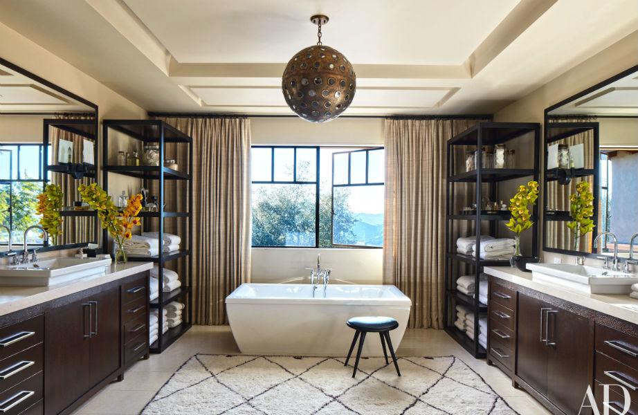 """Μέχρι και το μπάνιο έχει στυλ: το μεταλλικό φωτιστικό """"δένει"""" απόλυτα με το ξύλο που κυριαρχεί στο χώρο ενώ το χαλί δίνει μια αίσθηση πολυτέλειας."""