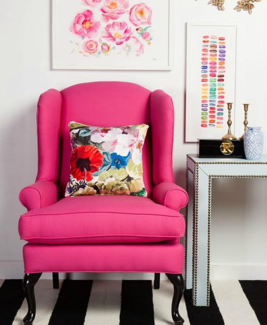Μια φούξια πολυθρόνα με ένα φλοράλ μαξιλαράκι δίνει χρώμα σε όλο το δωμάτιο.