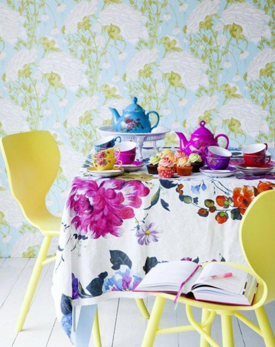Το πολύχρωμο τραπεζομάντιλο και οι πολύχρωμες καρέκλες δίνουν χρώμα στην κουζίνα.