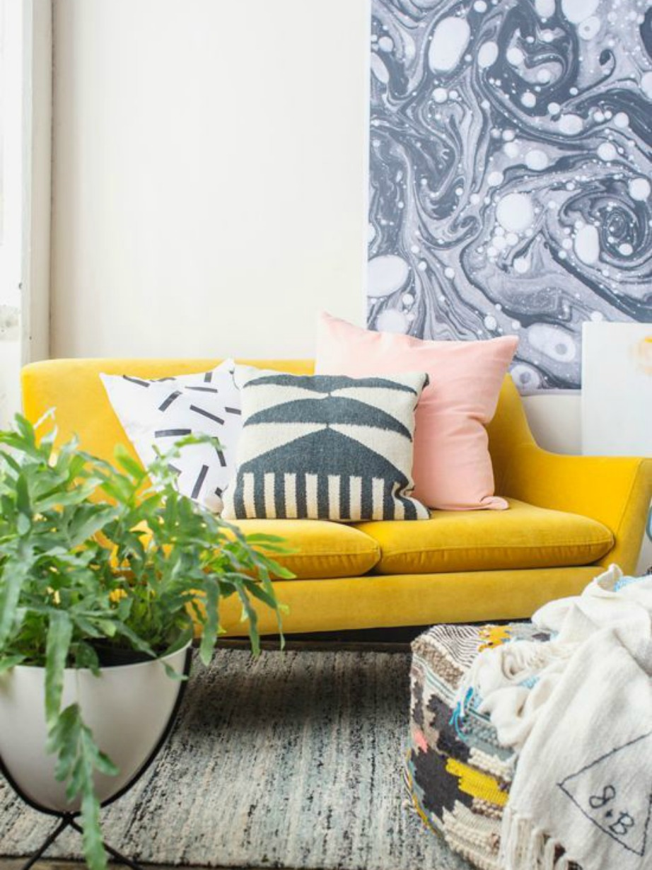 Ο έντονος κίτρινος καναπές έχει διακοσμηθεί με ουδέτερα μαξιλάρια για πιο ήπιο αποτέλεσμα.