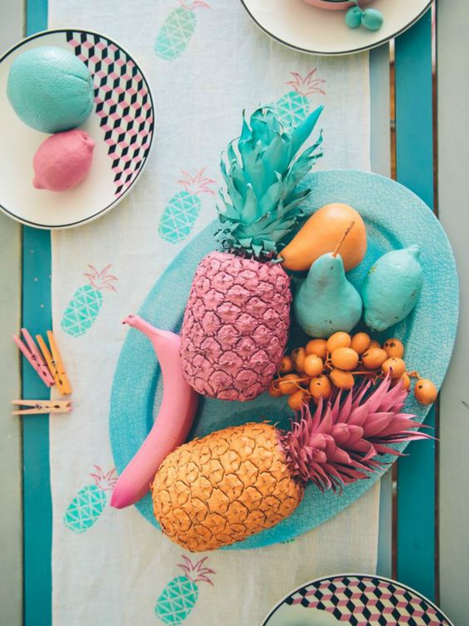 Μερικά ψεύτικα φρούτα βαμμένα σε διάφορα χρώματα δίνουν χρώμα στο τραπέζι της κουζίνας.
