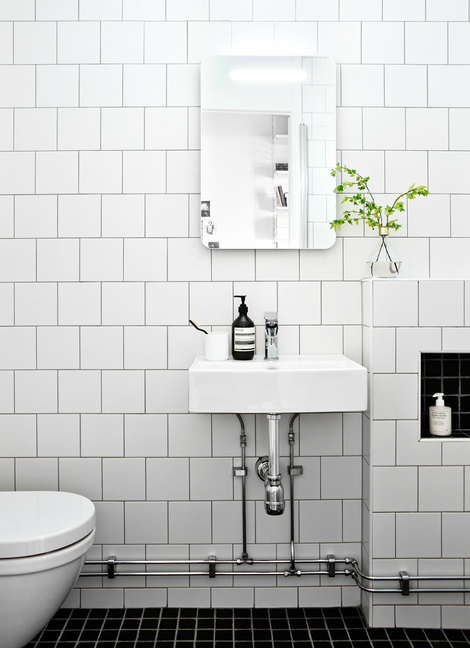 Τα λευκά πλακάκια στους τοίχους συνδυάζονται τέλεια με μαύρα πλακάκια στο πάτωμα του μπάνιου σας.