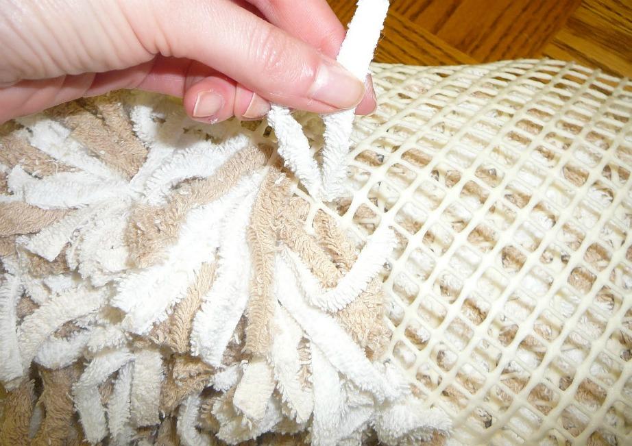 Κόψτε τις παλιές πετσέτες σε λωρίδες και περάστε τις μέσα από τις τρύπες του πλέγματος.