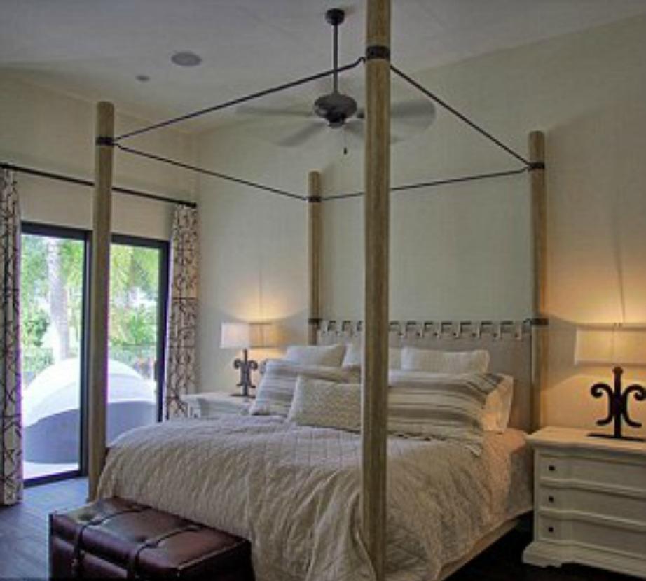 Το υπέρδιπλο κρεβάτι με ουρανό και λευκά κομοδίνα έρχεται σε αντίθεση με το σκούρο ξύλινο πάτωμα.
