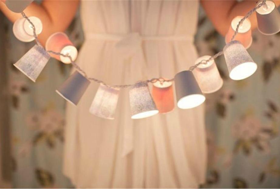 Χρησιμοποιήστε λαμπάκια και χάρτινα ποτήρια για να φτιάξετε την πιο φωτεινή γιρλάντα για το μπαλκόνι.