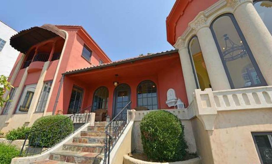 Εξωτερική άποψη της κατοικίας με το έντονο χρώμα, τους μαρμάρινους κίονες και τα πετρόχτιστα σκαλοπάτια.