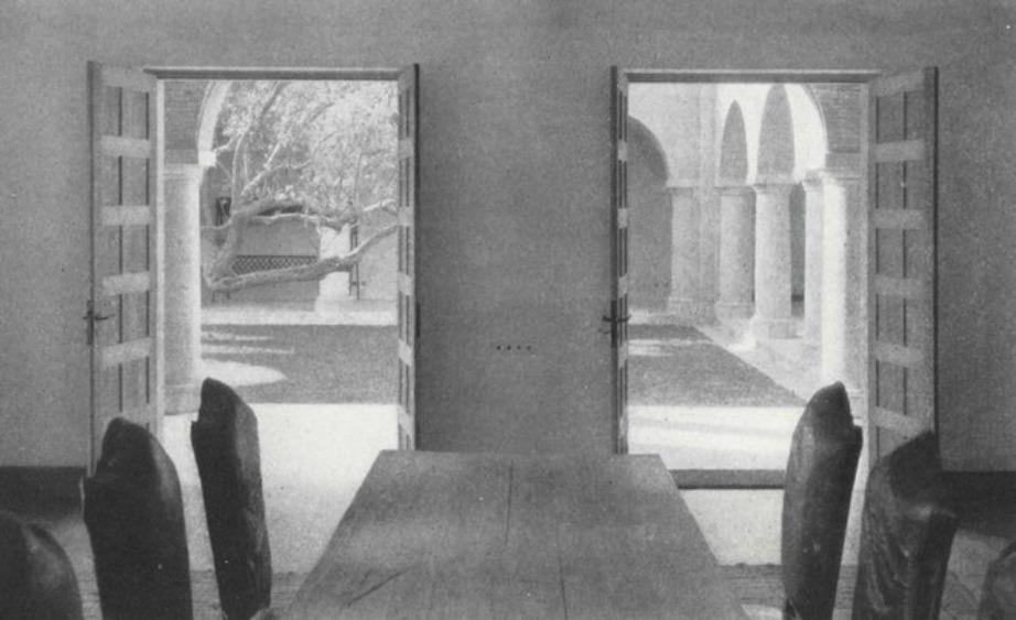 Τραπεζαρία με φόντο το εσωτερικό αίθριο της βίλας.
