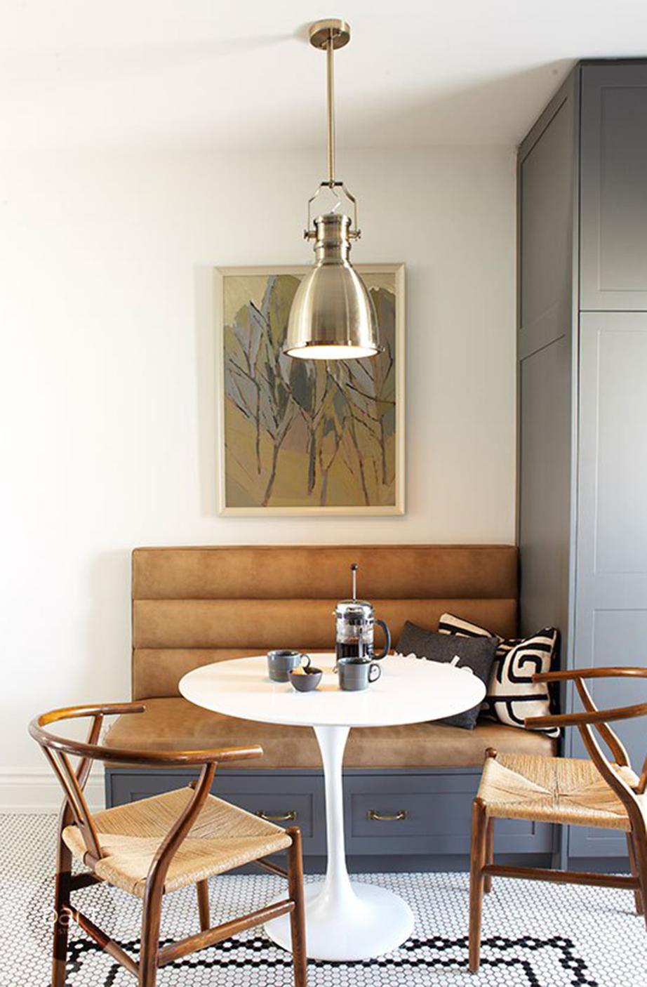 Εντειχιζόμενο έπιπλο με αποθηκευτικό χώρο στην ίδια απόχρωση με τα υπόλοιπα έπιπλα της κουζίνας και δερμάτινα καφέ καθίσματα αντικαθιστούν μαζί με το λευκό τραπέζι και τις ξύλινες καρέκλες την παλιά τραπεζαρία της κουζίνας.