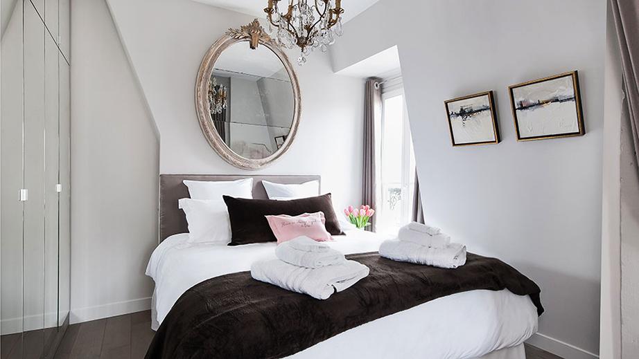 Λιτή η προσέγγιση για την κρεβατοκάμαρα με μόνα στοιχεία διακόσμησης έναν οβάλ καθρέπτη και ένα υπέροχο πολυέλαιο αντίστοιχης αποχρώσεως με τα μακρόστενα καδράκια που βρίσκονται στον πλαϊνό τοίχο.