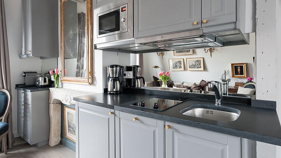 Γκρι απόχρωση για τα έπιπλα της κουζίνας, με inox ηλεκτρικές συσκευές και έναν καθρέπτη στον πάγκο της κουζίνας που μεγαλώνει, οπτικά, το χώρο.