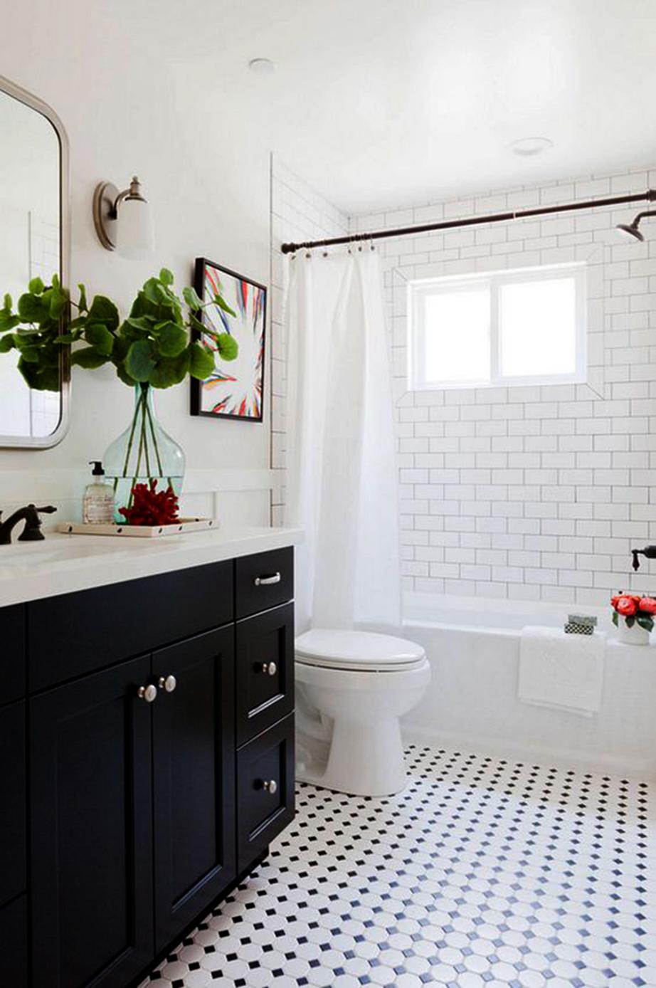 Το ένα και μοναδικό έπιπλο του μπάνιου σε μαύρη απόχρωση καταφέρνει να σπάσει την πολιορκία του λευκού.