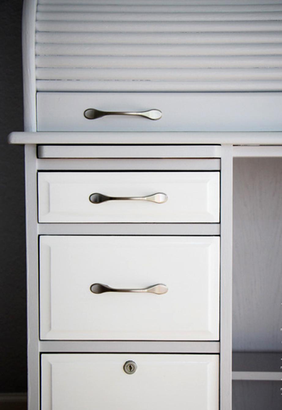 Απαλό, ανοιχτό γκρι και λευκό επιλέχθηκαν για την επένδυση του χρώματος στην εξωτερική επιφάνεια του επίπλου, ενώ μεταλλικές είναι πλέον οι λαβές των συρταριών.
