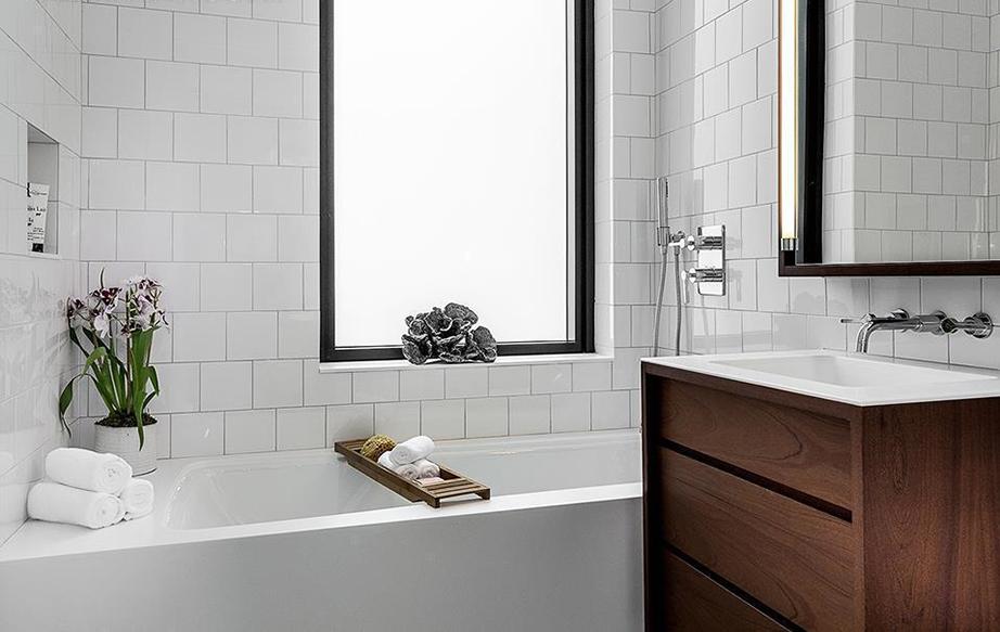 Ένα από τα μπάνια των υπνοδωματίων του διαμερίσματος όπου οι επιφάνειες του είναι καλυμμένες με λευκό πλακάκι και γκρι αρμό και ένα επιβλητικό έπιπλο από αφρικανικό μαόνι που ζεσταίνει χρωματικά και εικονικά την ατμόσφαιρα.