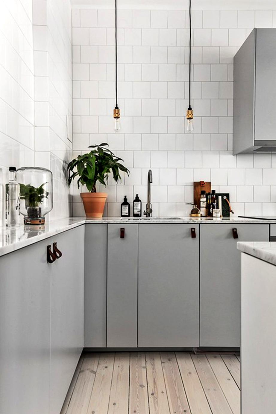 Βάψτε με ένα γκρι της επιλογής σας τα ντουλάπια της κουζίνας και κρατήστε λευκές τις υπόλοιπες σταθερές επιφάνειες αυτής. Χρησιμοποιήστε απλά ντουί με λάμπες αντί για φωτιστικά.