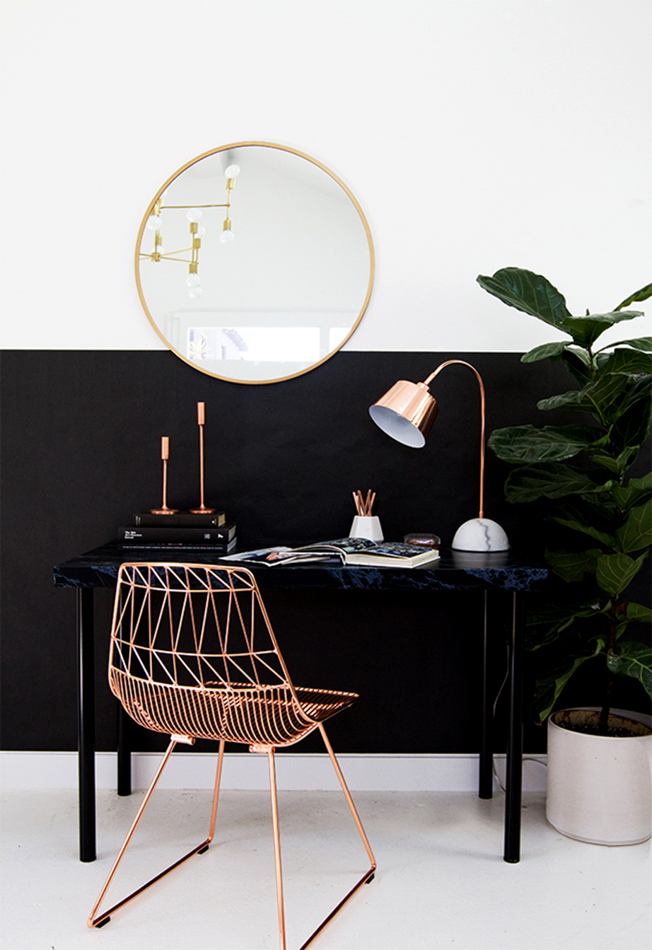 Τοποθετήστε ένα ματ βαμμένο γραφείο μπροστά από μια επιφάνεια με την ίδια απόχρωση και συμπληρώστε με μεταλλικά αντικείμενα χρώματος τόσο του χρυσού όσο και του χαλκού.