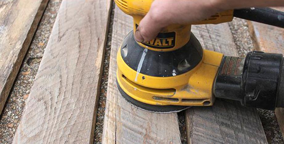 Ξεκαλουπώστε τις ξύλινες τάβλες από τις παλέτες και λειάνετε τις επιφάνειές τους με τη βοήθεια του τριβείου.