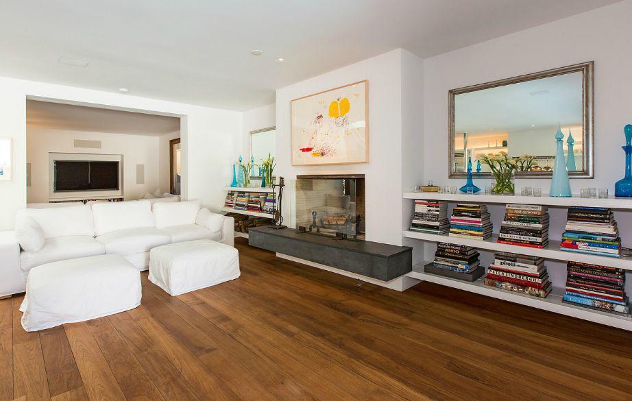 Οι άσπροι καναπέδες ταιριάζουν τέλεια με τα ξύλινα πατώματα του σαλονιού.