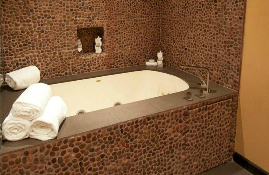 Το μπάνιο μοιάζει σαν ψηφιδωτό με τα αμέτρητα βοτσαλάκια που έχει.