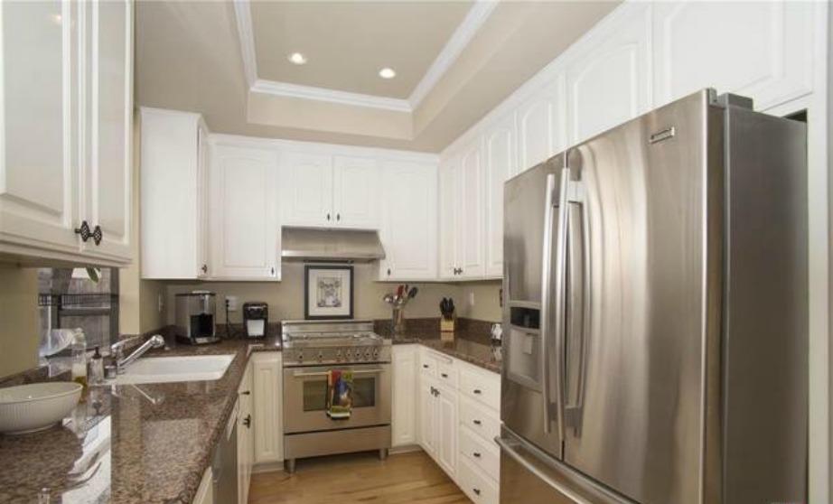 Με γρανίτη και ξύλινα λευκά ντουλάπια η κουζίνα μοιάζει λειτουργική