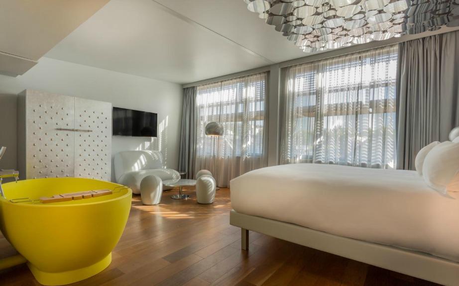 Το σήμα κατατεθέν του δωματίου είναι η καναρινή μπανιέρα στο κέντρο του δωματίου.