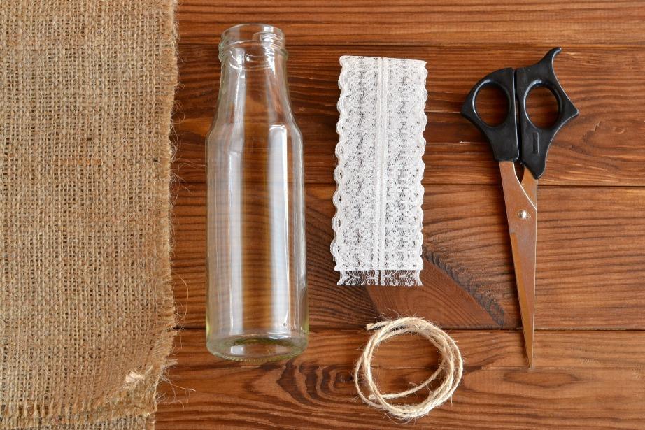 Τα υλικά που θα χρειαστείτε είναι λινάτσα, σπάγκος, δαντέλα, ψαλίδι και πιστόλη σιλικόνης.