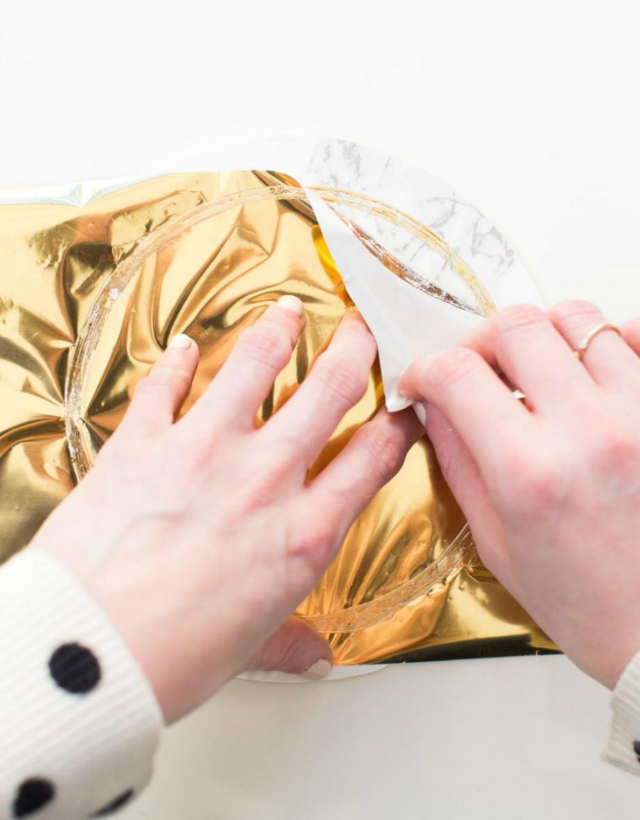 Μόλις στεγνώσει το υγρό τοποθετήστε πάνω το χρυσό χαρτί περιτυλίγματος.