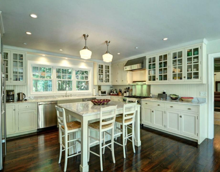Η εντυπωσιακή κουζίνα συνδυάζει το λευκό χρώμα με ξύλινες λεπτομέρειες.
