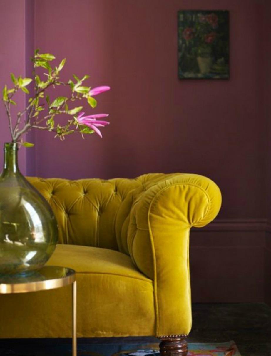 Ροζ τοίχοι, μουσταρδί καναπές και ροζ λουλούδια σε ένα βάζο αρκούν για ένα μοντέρνο αποτέλεσμα στο σαλόνι σας.